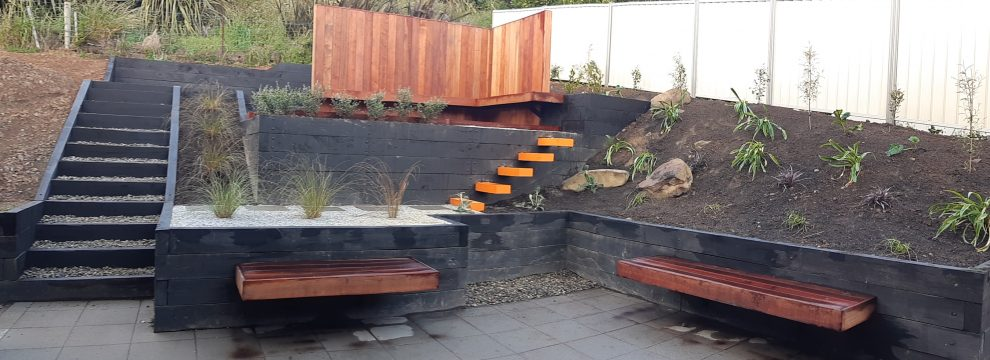This Neville Stewart design was built around beautiful and easy-to-use steps with plant borders, floating seats and a stunning wooden wall backdrop. The planting in the bank will fill out and largely obscure the fence behind it, creating a private and sheltered spot for enjoying sunny days.